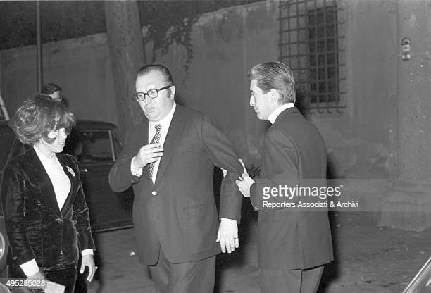 Italian film producer Franco Cristaldi holding by his arm Italian director Sergio Leone after the Vides party Beside them Leone's wife Carla Ranalli...