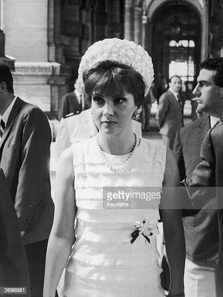Italian film star Gina Lollobrigida wears a sleeveless frilled summer dress in a style made popular by Christian Dior A pillbox hat in the same...