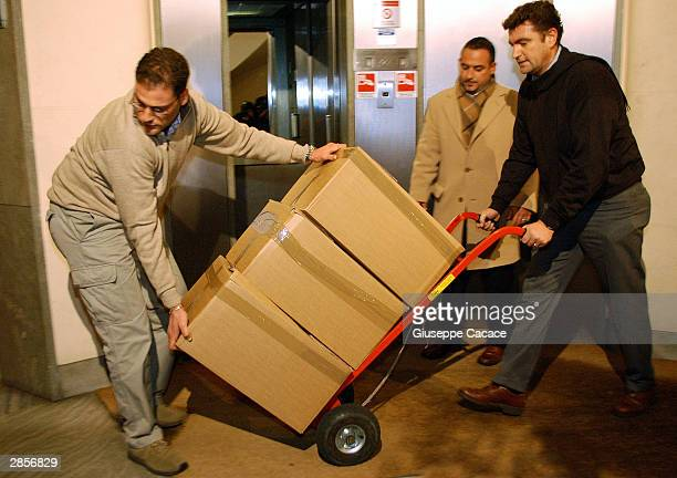 Italian financial police officers carry documents confiscated from the offices of Bank of America on January 9 2003 in Milan Italy At the request of...