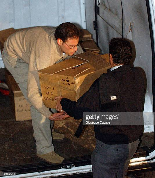Italian financial police officers load a van with documents confiscated from the offices of Bank of America on January 9 2003 in Milan Italy At the...