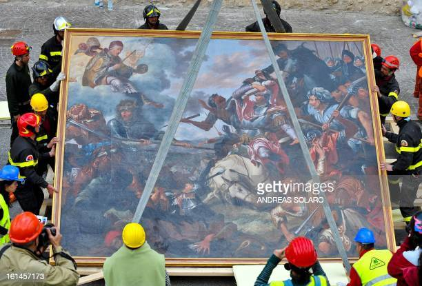 Italian firefighters carry 'The Battle of Celestine V' painting rescued from the damaged Santa Maria di Collemaggio's Basilica in L'Aquila on April...