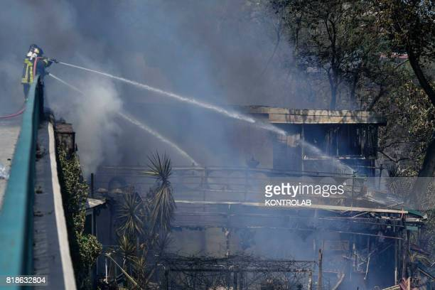 Italian firefighters pour water to put out a fire that broke out on the Posillipo hill in Naples. The fires continue to devastate Italy, especially...