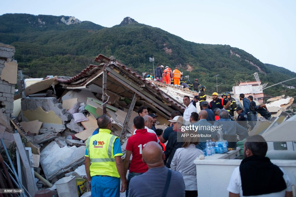 TOPSHOT - Italian firemen and emergency workers search through rubble of a collapsed house in Ischia, on August 22, 2017, after an earthquake hit the popular Italian tourist island off the coast of Naples, causing several buildings to collapse overnight. A magnitude-4.0 earthquake struck the Italian holiday island of Ischia, causing destruction that left two people dead at peak tourist season, authorities said, as rescue workers struggled early to free two children from the rubble. / AFP PHOTO / Eliano IMPERATO