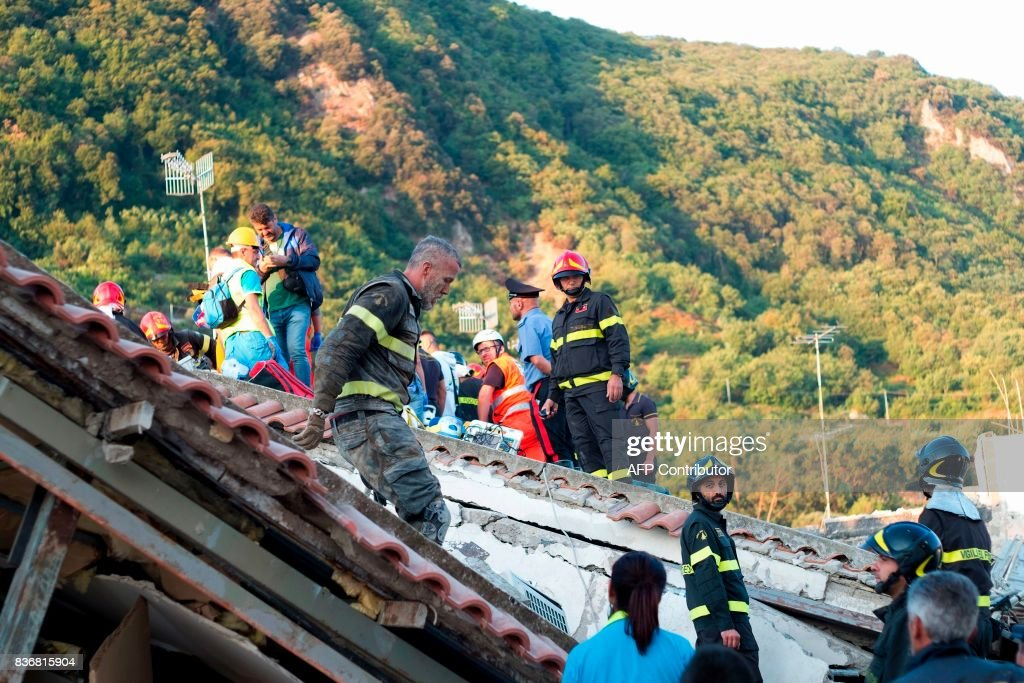 Italian firemen and emergency workers search through rubble of a collapsed house in Ischia, on August 22, 2017, after an earthquake hit the popular Italian tourist island off the coast of Naples, causing several buildings to collapse overnight. A magnitude-4.0 earthquake struck the Italian holiday island of Ischia, causing destruction that left two people dead at peak tourist season, authorities said, as rescue workers struggled early to free two children from the rubble. / AFP PHOTO / Eliano IMPERATO
