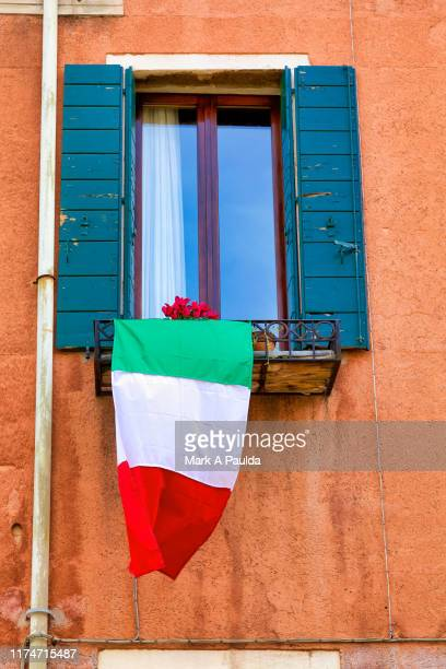 italian flag hanging from a window in venice - tricolore foto e immagini stock