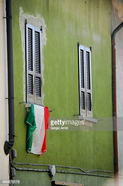 Italian flag hanging from a window on a green wall