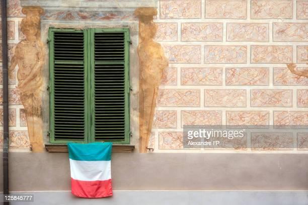 italian flag hung on window with closed shutters - bandera italiana fotografías e imágenes de stock