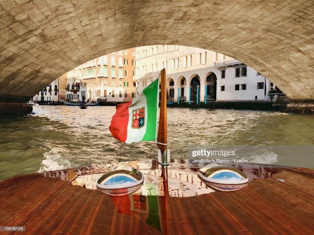 italian flag on water taxi under arch bridge in river stock photo