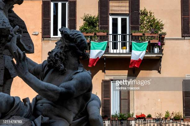 Italian flags on a balcony behind the fountain of the Four Rivers by Gian Lorenzo Bernini at Navona square during Italy's lockdown due to Covid19...