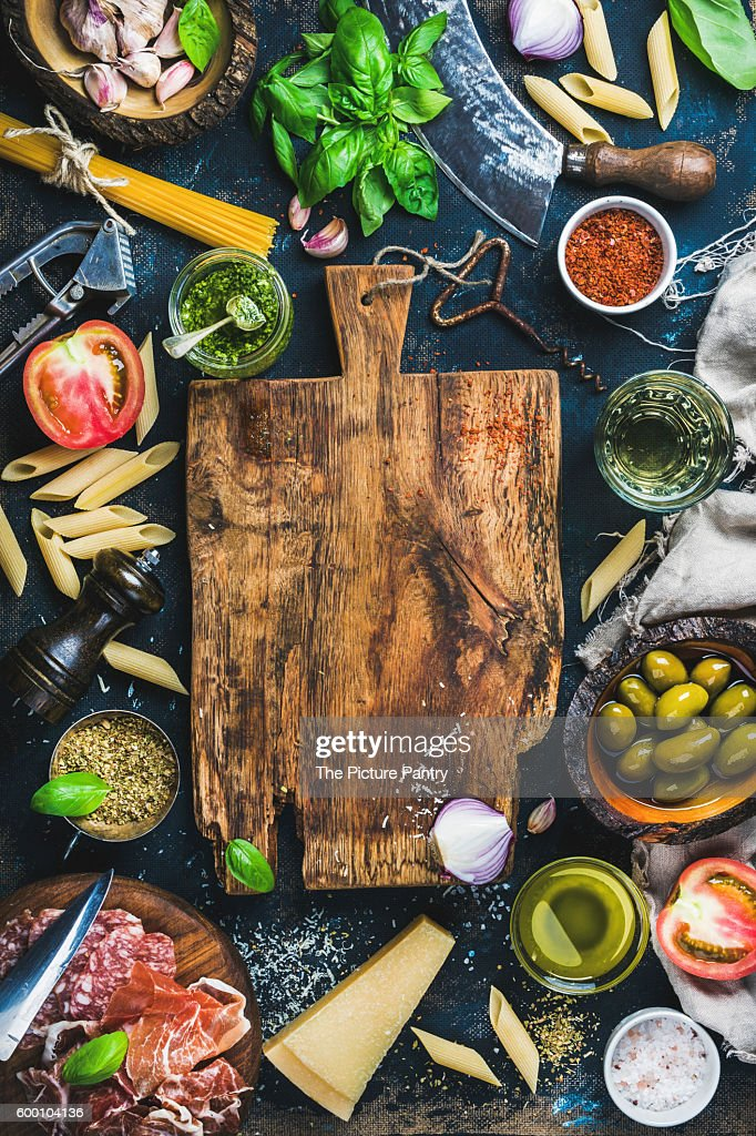 Italian Food Cooking Ingredients On Dark Background With Rustic Wooden Chopping Board In Center Stock