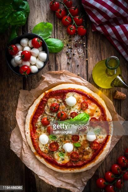 italian food: delicious homemade pizza with mozzarella and cherry tomatoes - pizza margherita foto e immagini stock
