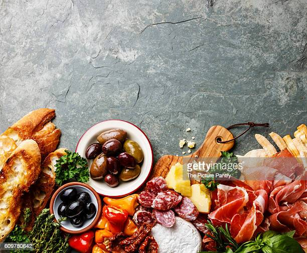 Italian food ingredients background with ham, salami, parmesan, olives, bread sticks on stone slate