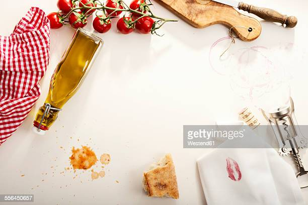 Italian Food, Olive oil bottle, baguette, napkin with lipstick, corkscrew and tomatoes