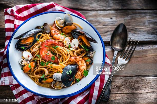 italian food: seafood pasta shot from above on rustic wooden table - seafood stock pictures, royalty-free photos & images