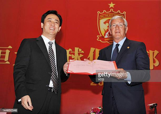 Italian football coach Marcello Lippi receivers an engagement letter from Xu Jiayin Chairman of Evergrande Real Estate Group during a press...