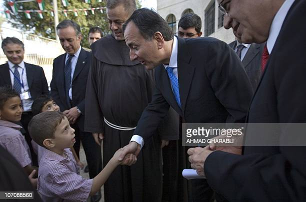 Italian Foreign Minister Franco Frattini shakes hands with a Palestinian pupil during a visit to the Terra Sancta School in the Palestinian West Bank...