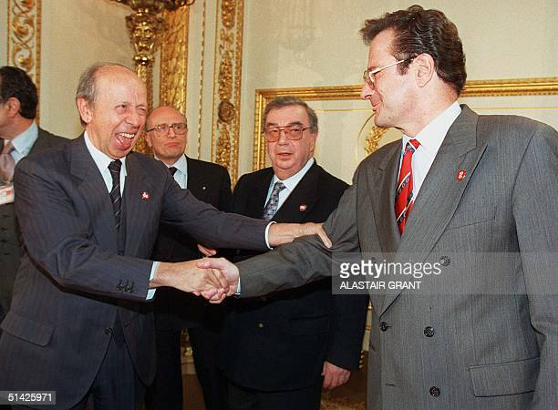 Italian Foreign Minister Lamberto Dini reaches out to shake the hand of his German counterpart Klaus Kinkel , while Russian Foreign Minister Yevgeny...
