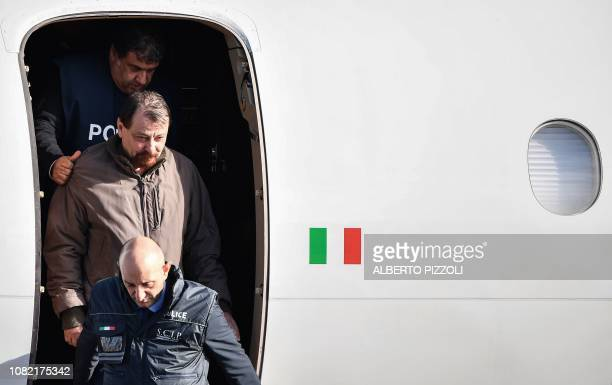 Italian former communist militant Cesare Battisti wanted in Rome for four murders attributed to a farleft group in the 1970s is escorted by Italian...