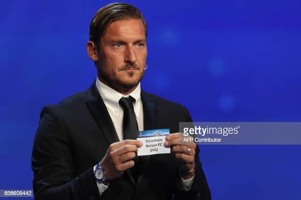 Italian former football player Francesco Totti shows the sheet of paper bearing the name of Tottenham Hotspur FC during the UEFA Europa League group...