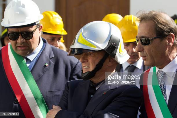 Italian former Prime Minister and president of right-wing party Forza Italia, Silvio Berlusconi wears an helmet of Italian firemen on October 14,...