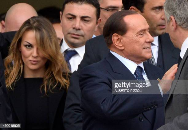 Italian former Prime Minister Silvio Berlusconi flanked by his girlfriend Francesca Pascale leaves after the People of Freedom party's national...