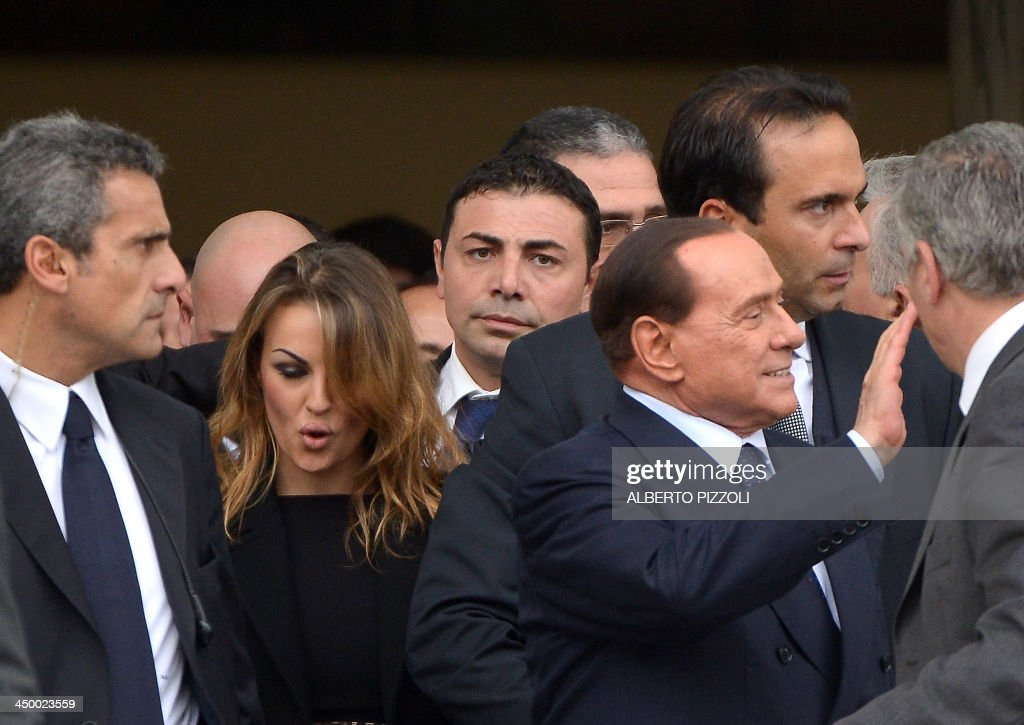 Italian former Prime Minister Silvio Berlusconi (R), flanked by his girlfriend Francesca Pascale (2nd L), leaves after the People of Freedom (PDL) party's national convention in Rome on November 16...