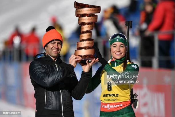 Italian former professional road bicycle racer Gilberto Simoni and Italian biathlete Dorothea Wierer hold the trophy of the 2019 Giro d'Italia...