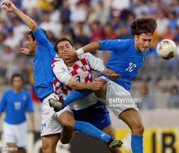 Italian forward Francesco Totti fights for an aeriall ball with Croatian defender Josip Simunic and teammate Italian forward Christian Vieri during...