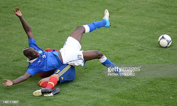 Italian forward Mario Balotelli falls on a Spanish palyer during the Euro 2012 championships football match Spain vs Italy on June 10 2012 at the...