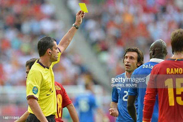 Italian forward Mario Balotelli is given a yellow card by Hungarian referee Viktor Kassai during the Euro 2012 championships football match Spain vs...