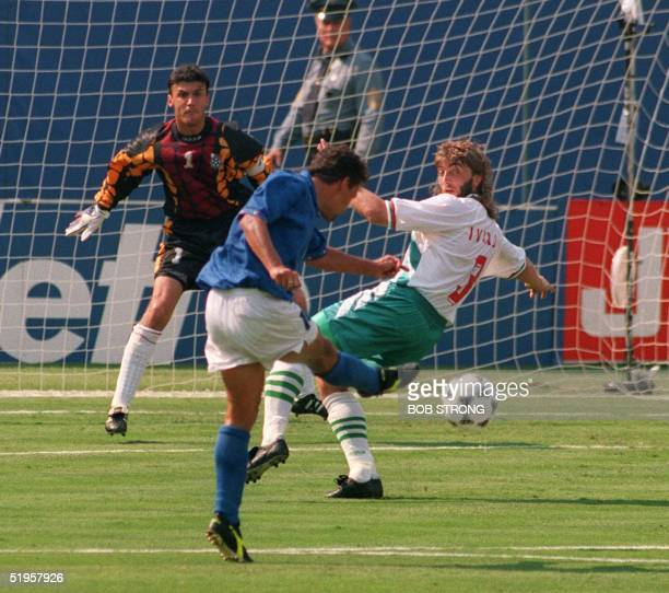 Italian forward Roberto Baggio kicks the ball past Bulgarian defender Trifon Ivanov and goalkeeper Borislav Mihaylov to score his first goal during...