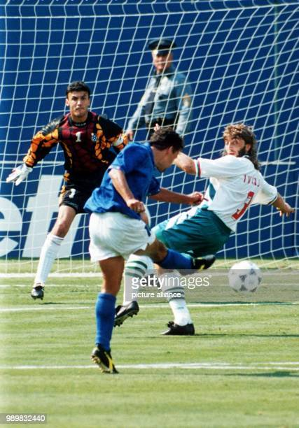 Italian forward Roberto Baggio kicks the ball past Bulgarian defender Trifon Ivanov as he is about to score the 10 goal while Bulgarian goalkeeper...