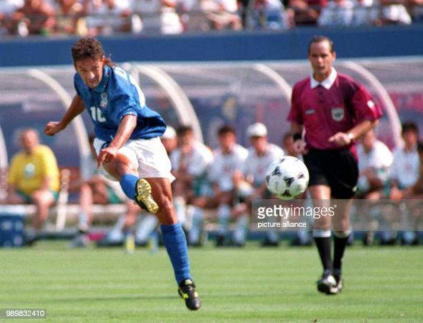 Italian forward Roberto Baggio throws his leg into the air and kicks the ball while French referee Joel Quiniou watches the scene during the 1994...