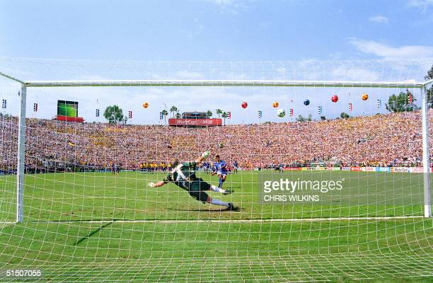 Italian forward Roberto Baggio watches his penalty kick go over the crossbar as Brazilian goalkeeper Claudio Taffarel dives the wrong way during the...