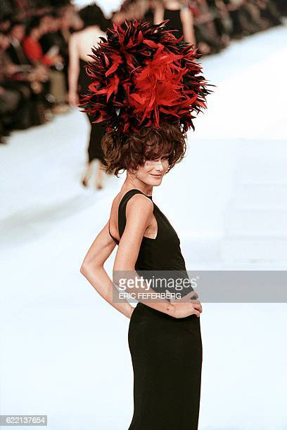 Italian French model Carla Bruni displays a long black dress and a red and black feathered hat designed by Karl Lagerfeld for Chanel as part of his...