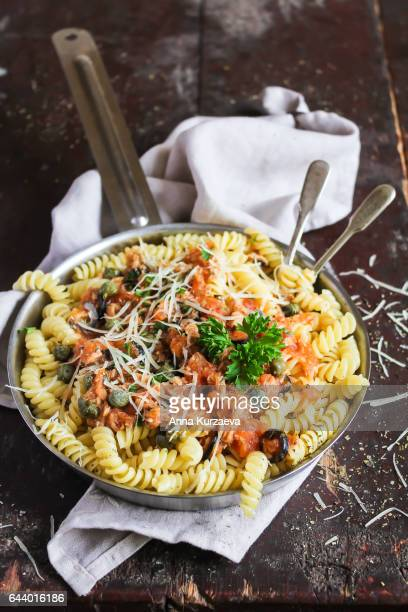 Italian fusilli pasta dish with tuna fish fillet, tomato sauce, capers and cheese in a pan on a wooden table, selective focus