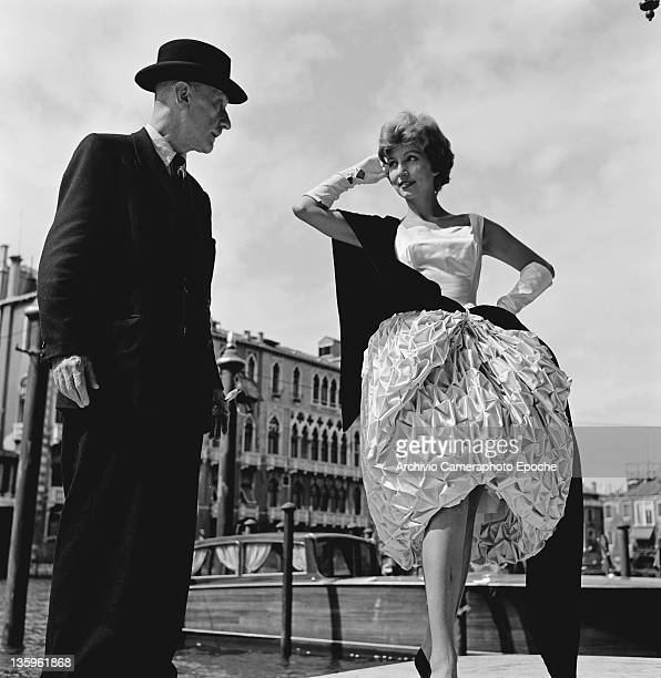 Italian Futurist photographer and filmmaker Anton Giulio Bragaglia with a woman modelling a puffball skirt by Mingolini and Guggenheim outside the...