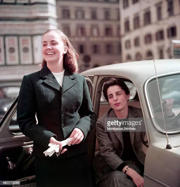 Italian girls Maria Novella Stiozzi Ridolfi and Lucia Serena Benini joking in piazza del Duomo beside a car Florence 1955