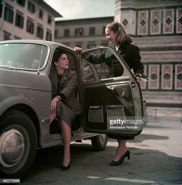 Italian girls Maria Novella Stiozzi Ridolfi and Lucia Serena Benini chatting in piazza del Duomo beside a car Florence 1955