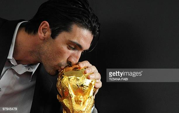 Italian goalkeeper and 2006 world champion Gianluigi Buffon kisses the World Cup trophy at Rome Airport Fiumicino on March 7 2010 The Football World...