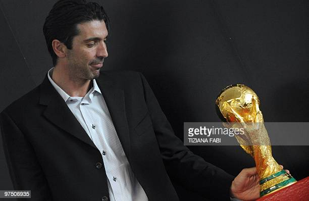 Italian goalkeeper and 2006 world champion Gianluigi Buffon touches the World Cup trophy at Rome Airport Fiumicino on March 7 2010 The Football World...