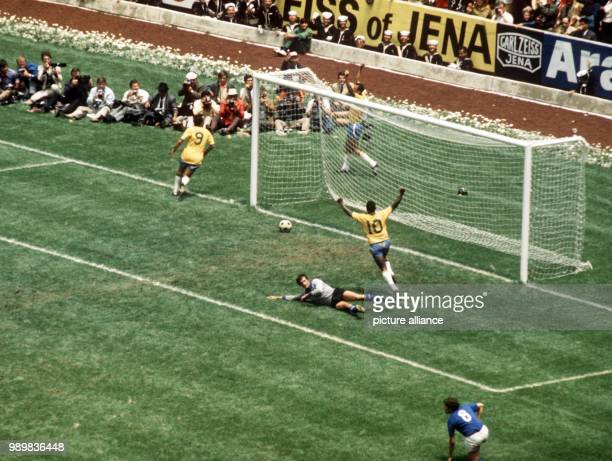 Italian goalkeeper Enrico Albertosi lies defeated on the pitch as the ball rolls back out of his goal Brazilian scorer Carlos Alberto throws his arms...