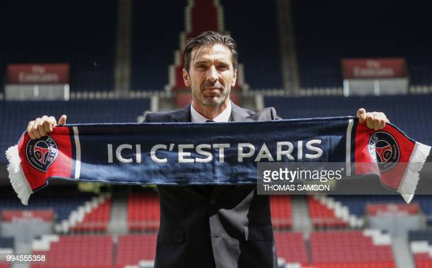 TOPSHOT Italian goalkeeper Gianluigi Buffon poses with his new club's scarf on July 9 2018 at the Parc des Princes stadium in Paris after French...
