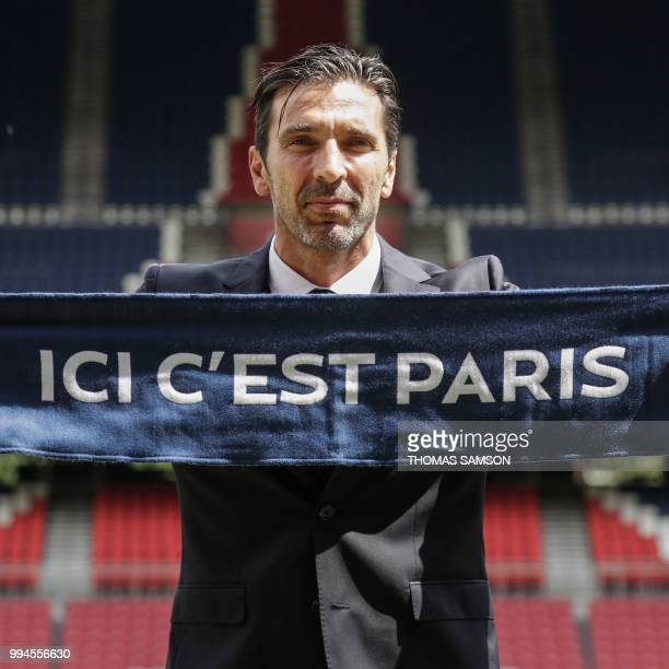 Italian goalkeeper Gianluigi Buffon poses with his new club's scarf on July 9 2018 at the Parc des Princes stadium in Paris after French Ligue 1...