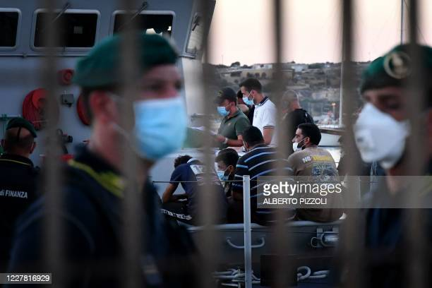 Italian Guardia di Finanza police officers control migrants upon their arrival on the Italian Pelagie island of Lampedusa on July 28 2020 Hundreds of...