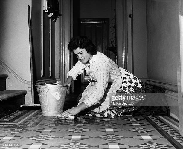 Italian housemaid Amelia Carlesimo cleans the floor of Sandford Hall which her employers are giving her the run of for her honeymoon week as a...