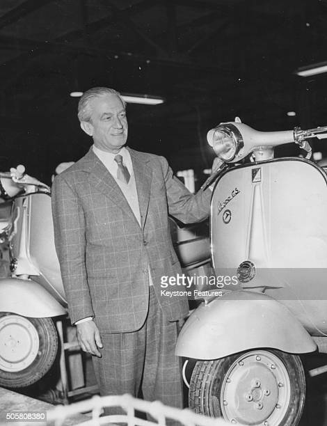 Italian industrialist Enrico Piaggio manufacturer of Vespa scooters pictured with one of the motor scooters at a Messerschmitt factory Germany...