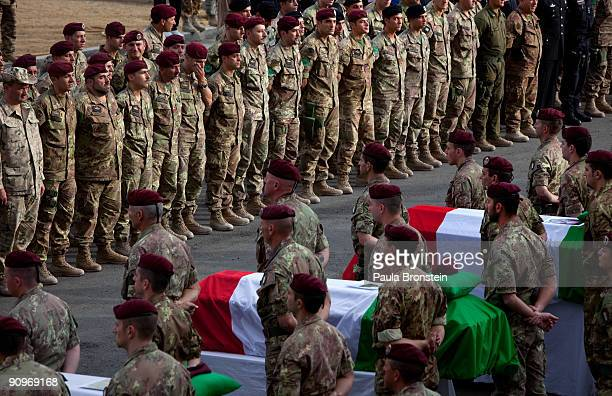 Italian ISAF soldiers stand at attention during a memorial service for the six soldiers killed after a suicide car bomb hit a military convoy on the...