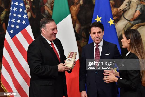 Italian journalist Alice Martinelli from Italy's Mediaset television programm Le Iene hands to US Secretary of State Mike Pompeo a piece of Parmesan...