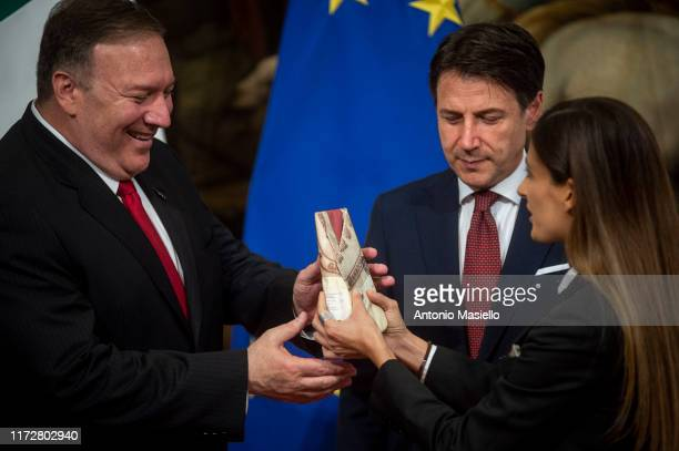 Italian journalist Alice Martinelli of the television program Le Iene hands to US Secretary of State Mike Pompeo a piece of Parmesan cheese during...